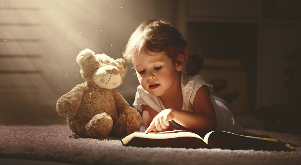 young child reading with teddy bear soft toy