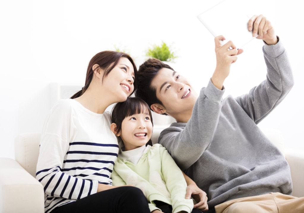 father mother and child taking a selfie