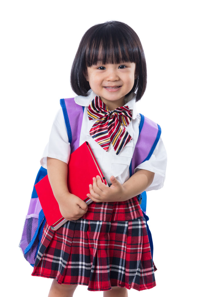 young girl in school uniform and holding a book
