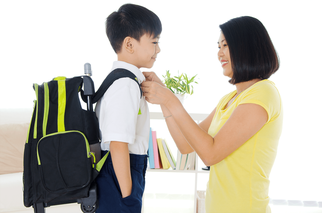 mother buttoning uniform shirt of young boy student carrying bagpack