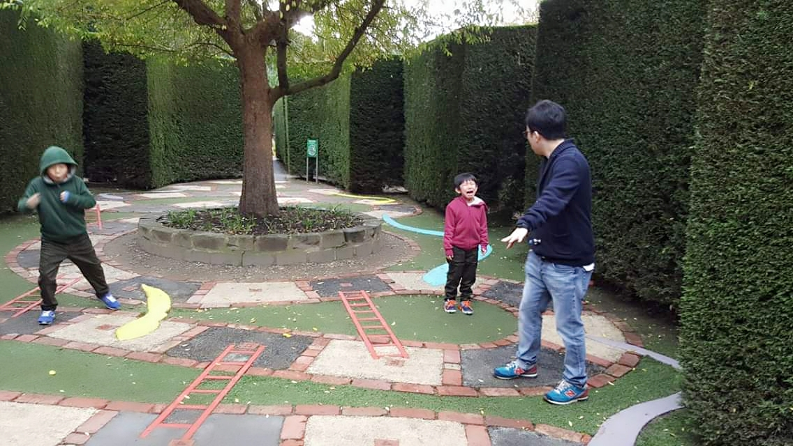 family playing snakes and ladders game in enchanted garden Melbourne