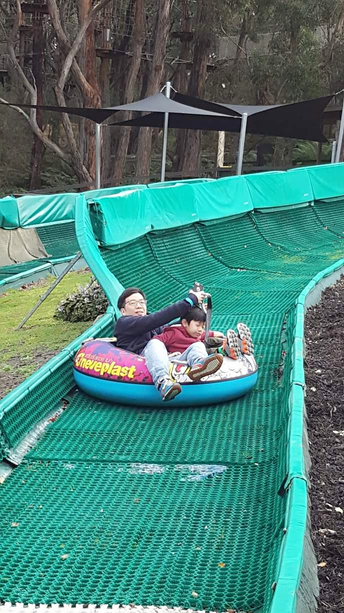 father and son float sliding in enchanted garden melbourne