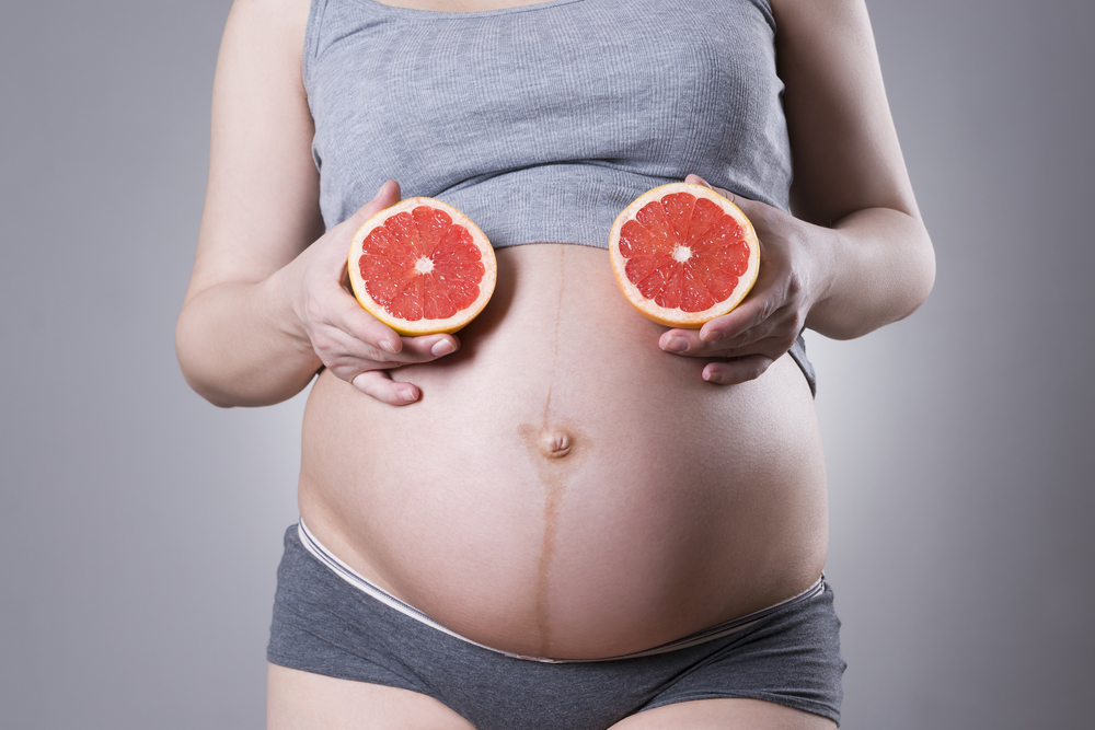 week 23 exposed pregnant belly with grapefruits