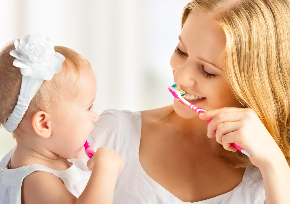 baby first teeth brushing with mother