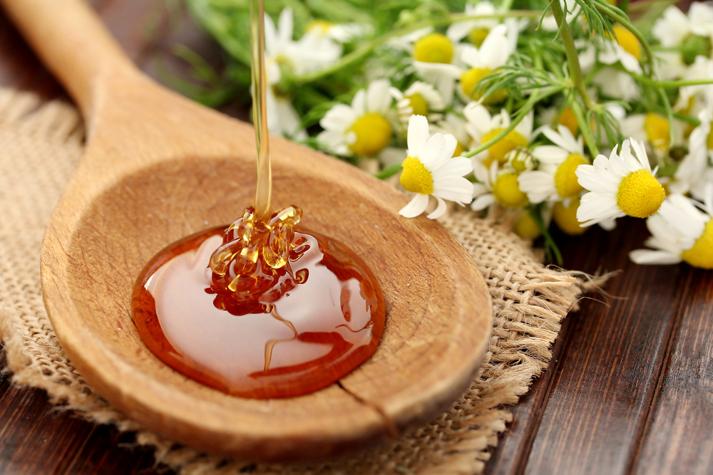 manuka honey in wooden spoon with flowers