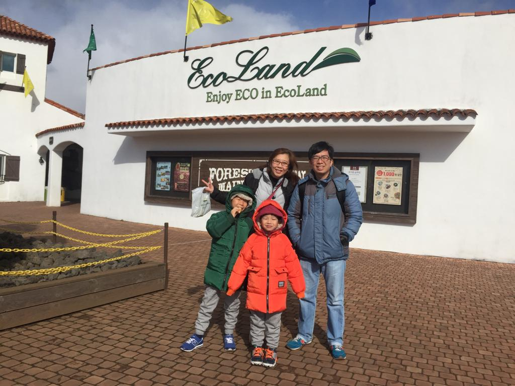 Family photo with Ecoland Jeju sign and entrance